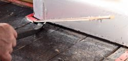 man using crowbar to uplift red gripper roads from floor