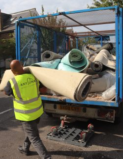 anyjunk waste contractor carrying roll of carpet to van to dispose of