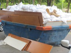 overfilled skip with wooden planks on the side
