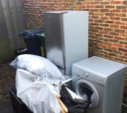 a bulky waste collection including black bin bags refuse sacks fridge and washing machine white appliances